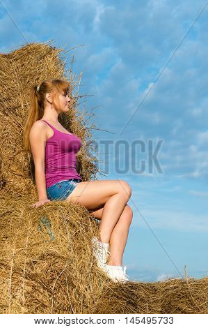 сharming woman sitting on haystack on nature