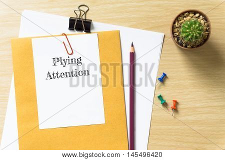 Plying attention, message on the white paper / business concept / wood desk , copy space / business concept / view from above, top view