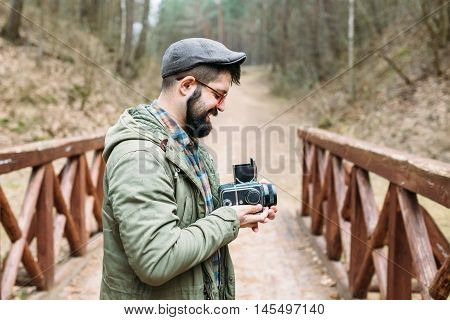 Portrait in profile of a nice smiling male photographer with film cameras on a wooden bridge in a picturesque forest life style hipster trips