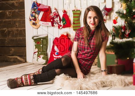 Young Girl Sitting Next To Christmas Tree And Gifts