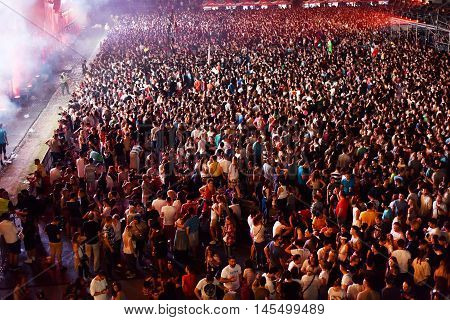 Large Crowd Of People At A Concert In The Front Of The Stage