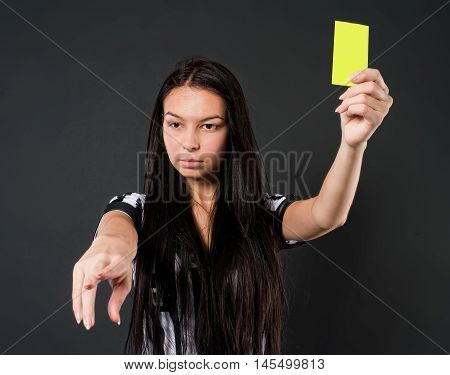 Young beautiful Soccer Referee shows yellow card