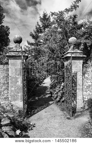 Old Wrought Iron Full Size Garden Gate And Brick Wall In Black And White