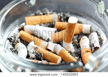 Cigarette Butts With Ash In Ashtray On Black Background
