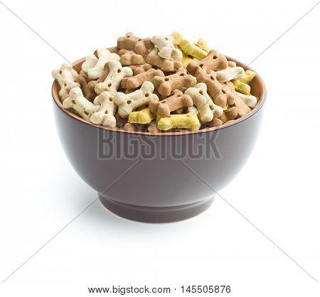Dog food shaped like bones in bowl isolated on white background.