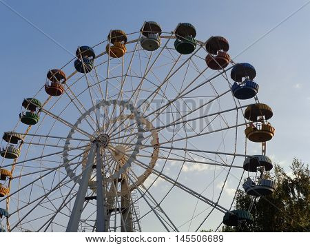 Ferris wheel with colored cabins on a background of blue clear sky