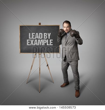 Lead by example text on  blackboard with businessman wearing boxing gloves