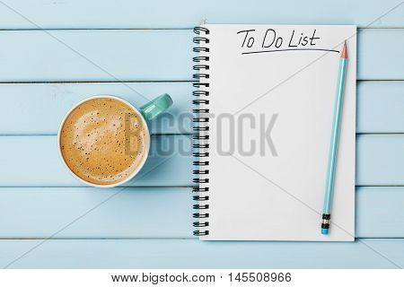Coffee cup and notebook with to do list on blue rustic desk from above. Planning and design concept.