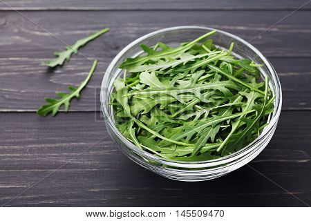 Rucola salad, rucoli, rugula, colewort, roquette or arugula on wooden black rustic table.