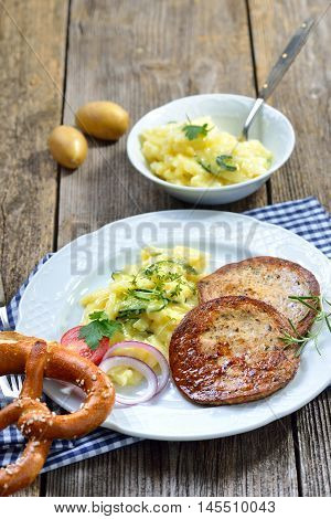 Bavarian food: Fried slices of sausage with pieces of pig spleen (so called 'Milzwurst') served with potato salad and a pretzel