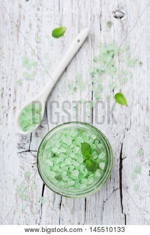 Sea salt bath scented mint for spa and aromatherapy on white wooden background, rustic style, top view. Flat lay.