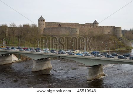 IVANGOROD, RUSSIA - MAY 01, 2015: Border crossing bridge between Russia and Estonia through the Narva river on the background of the Ivangorod fortress cloudy day