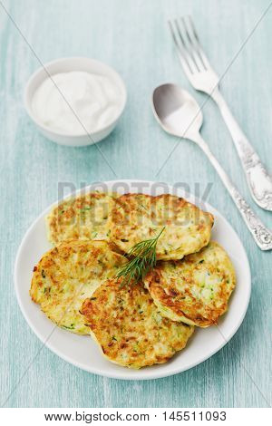 Vegetable zucchini cabbage pancakes or fritters with sour cream on wooden kitchen table.