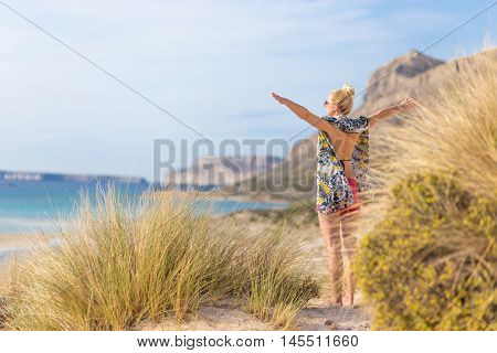 Relaxed woman wearing colorful scarf, enjoying sun, freedom and life at beautiful Balos beach in Greece. Concept of holidays, vacations, freedom, joy and well being.