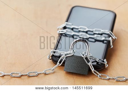 Smartphone or mobile tied chain with lock on wooden table gadget and digital devices. Detox concept.