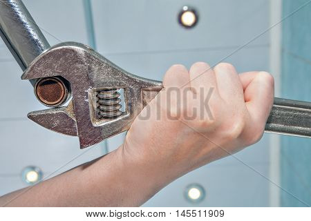 Unscrew the old wrong clogged faucet aerator using an adjustable wrench plumber hands handyman close-up.