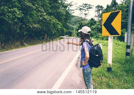 Young girl with hat and backpack hitchhiking on the road