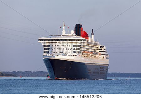 Stade, Germany - August 30, 2016: Luxury cruise ship RMS Queen Mary 2 on Elbe river heading to Southampton.
