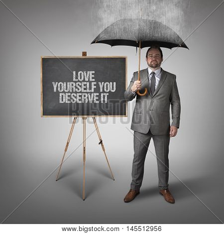 Love yourself you deserve it text on blackboard with businessman and umbrella