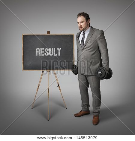 Result text on blackboard with businesssman holding weights