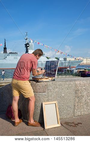 ST. PETERSBURG, RUSSIA - JULY 28, 2016: the Artist paints a picture with a military ship on the Admiralty embankment in Saint-Petersburg