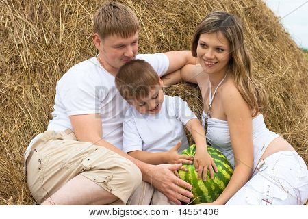 Happy Family In Haystack Or Hayrick With Watermelon