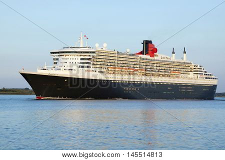 Stade, Germany - August 30, 2016: Luxury cruise liner RMS Queen Mary 2 departing from Hamburg to Southampton on Elbe river in evening sunlight.