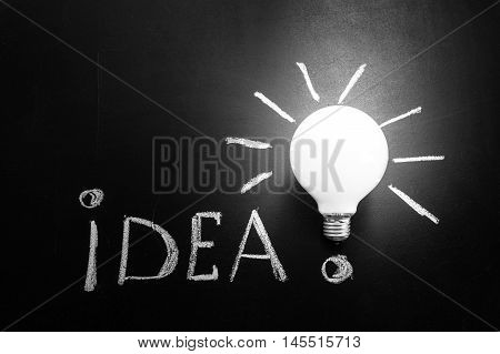 Light bulb with rays on the black chalkboard with title idea! written by white chalk light bulb idea business idea business concept Innovation concept