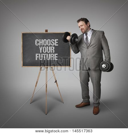 Choose your future text on blackboard with businessman holding weights