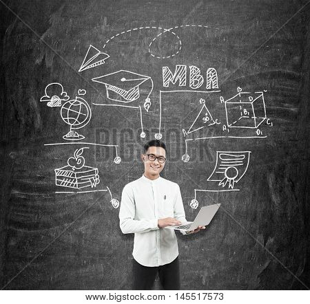 Asian man with laptop standing near blackboard with MBA sketch. Concept of manager's work