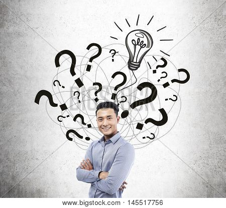 Smiling Asian man standing near concrete wall with light bulb and question marks sketches. Concept of solution finding