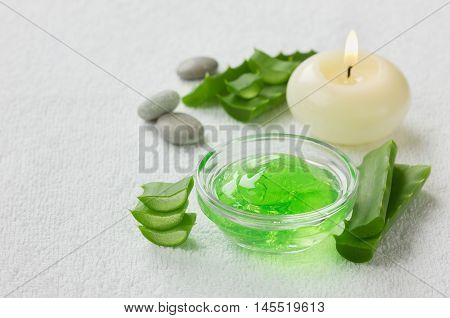 Fresh aloe vera leaf and aloe gel with burning candles on white surface. Cosmetic and spa concept, space for text.