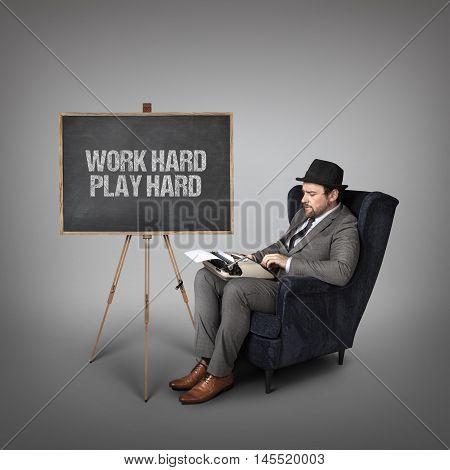 Work hard play hard text on  blackboard with businessman and key
