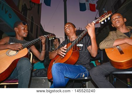 SANTO DOMINGO, DOMINICAN REPUBLIC - January 24, 2016: Street artist playing guitar, street life of Calle el Conde and Colonial Zone of Santo Domingo.
