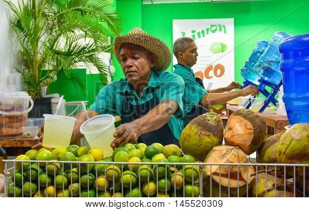 SANTO DOMINGO, DOMINICAN REPUBLIC - January 24, 2016: Barman of lemon and coconut juice, street life of Calle el Conde and Colonial Zone of Santo Domingo.