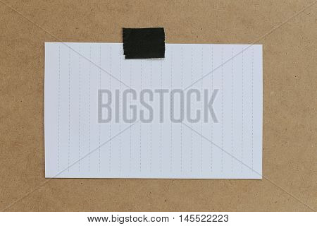 vintage of note paper on brown background and copy specs you can input text to it.