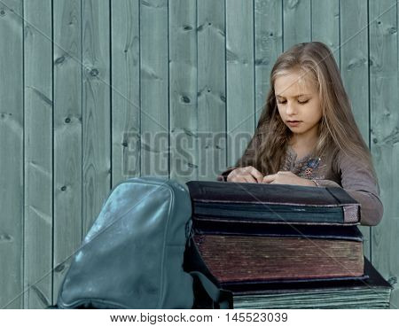 vintage children. old albums. Girl with books and backpack on a wooden background
