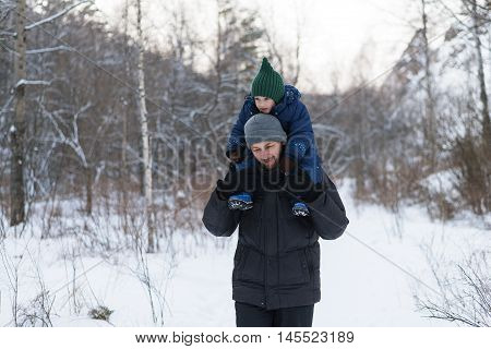 Father and child walking in a winter forest. The child is sitting on fathers' shoulders.