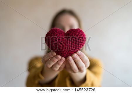 Woman with a crocheted heart. Soft focus on a heart. Woman is unfocused.