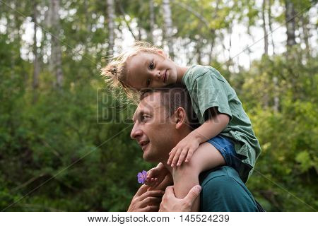 Little girl sitting on her father's shoulders in a summer forest.