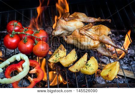 Grilling delicious poultry quails and fresh juicy vegetables in a restaurant on barbecue. Partridge, quail, potato, tomato, sweet pepper are prepared on the grill on sunny day. Culinary concept with delicious food.