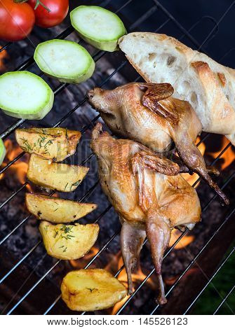 Grilling delicious poultry quails and fresh juicy vegetables in a restaurant on barbecue. Partridge, quail, potato, tomato, zucchini are prepared on the grill on sunny day. Culinary concept with delicious food.