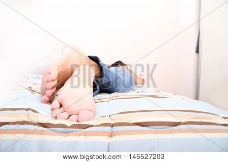 A young adult woman lying on the Bed.