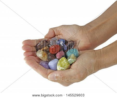 Choose the stones you are attracted to - Female  cupped hands full of tumbled multicolored healing crystals on a white background