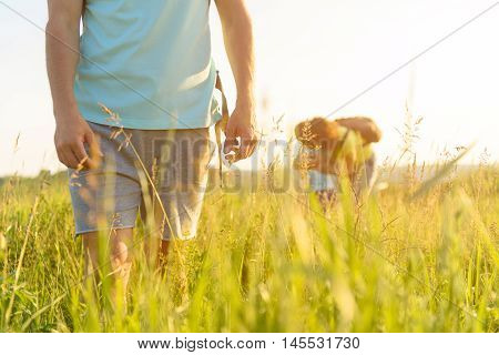 Keeping up with me. Cropped photo of adult man walking along field with his wife and daughter in background