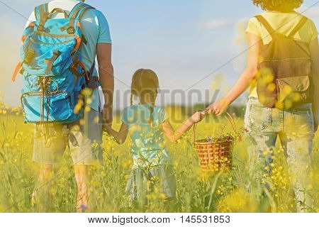 She loves her mom and dad. Rear view shot of young family walking through field together and holding basket with wildflowers