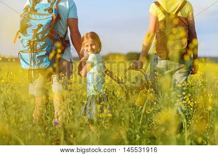 This is my family. Cropped photo of little girl holding her parents hands, helping her mother to carry basket of wild flowers and smiling at camera