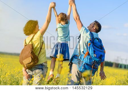 Enjoying sunshine. Cute young family spending time together outdoors with backpacks, holding up little daughter by her hands