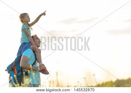 Dad, look there. Adult man standing outside and carrying on shoulders his daughter, which showing away into distance