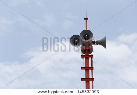 Loudspeakers broadcast alarms on outdoor sky background.
